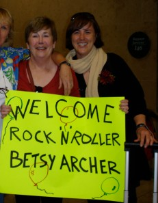 "two women smiling, one holding sign ""Welcom Rock N Roller Betsy Archer"""