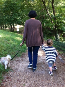Woman, dog and littl boy walking on a wooded path