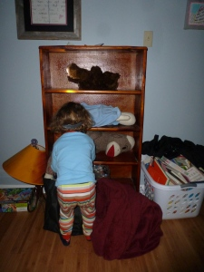 little boy with headlamp putting dolls on shelves of bookself