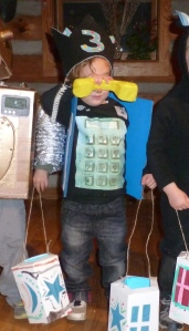 Little boy with third birthday crown covering his face, wearing payphone costume